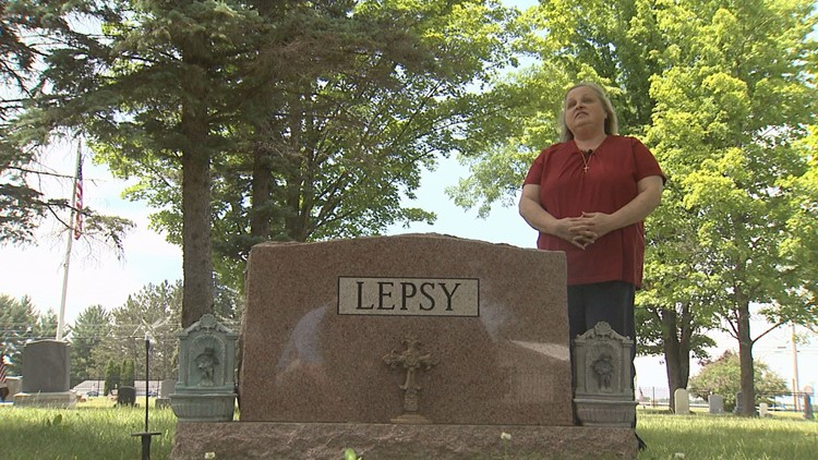 Lisa Lepsy standing over her mother's grave in a Grayling, Michigan cemetery.