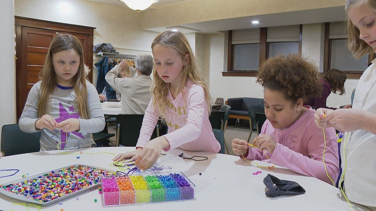 Brynn's church friends help make bead strands.
