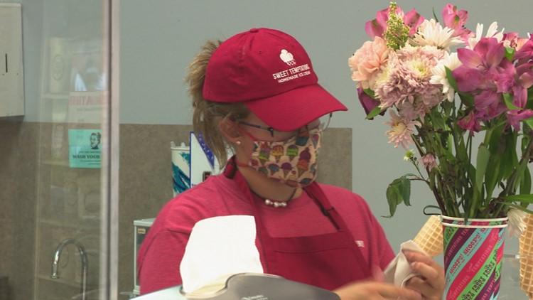 Woman gives flowers to teen who faced customers angry about masks at ice cream shop