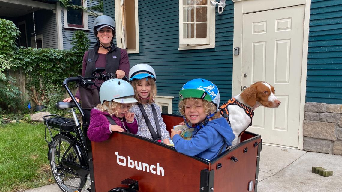 GR Mom saves time and money by biking her kiddos to school while they read
