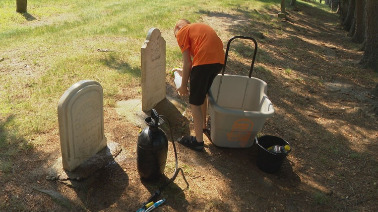Navene cleans two of his relatives gravestones.