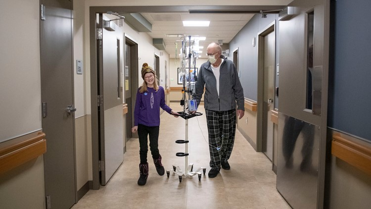 Brynn and grandpa walking on the cancer floor of Butterworth Hospital.